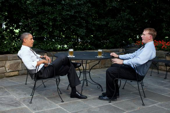 U.S. President Obama enjoys a beer with Medal of Honor winner Meyer on the patio outside of the White House Oval Office in this handout photograph