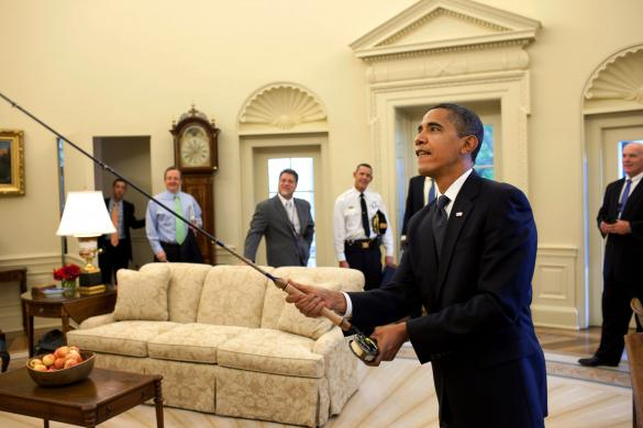 President Barack Obama tries out the fly fishing rod given to him on his birthday by a group of avid fisherman on his staff in the Oval Office
