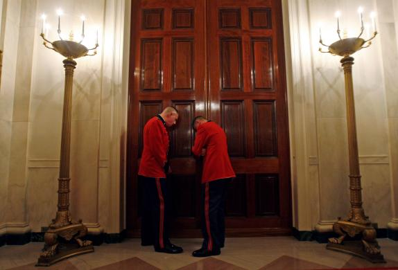 Members of The President's Own United States Marine Band listen through a door as musician Stevie Wonder performs in Washington