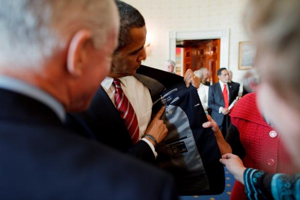 U.S. President Obama displays label of his suit as he meets with labor leaders in handout photo taken in Blue Room of the White House in Washington